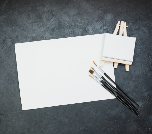 Blank white paper with mini easel and paintbrush on slate backdrop
