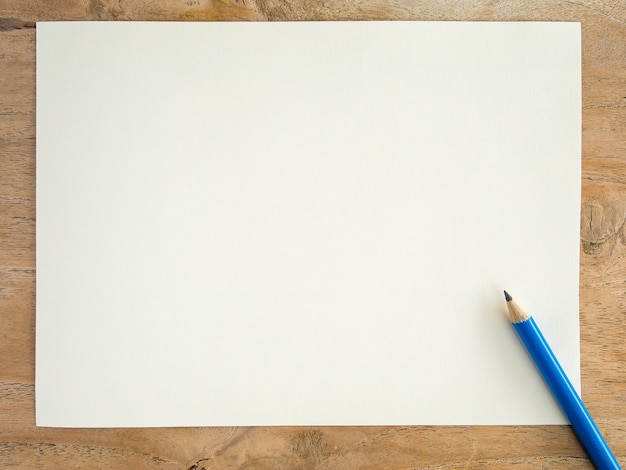 Blank white paper with pencil on wood table