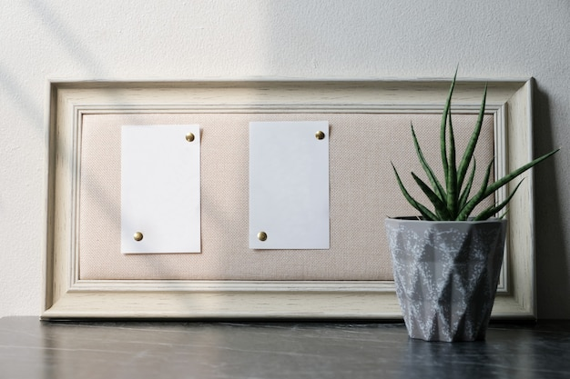 Blank white papers on brown vintage wooden frame hanging on black and white marble wall