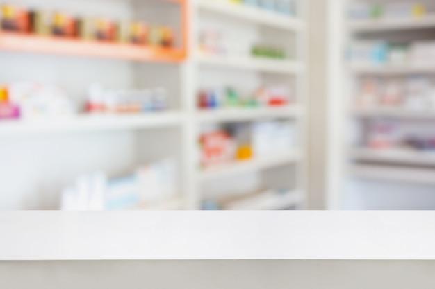 몽타주 의료 제품 디스플레이를 만들기 위해 약국 약국 배경에서 약물의 흐림 선반이있는 빈 흰색 약국 테이블 카운터