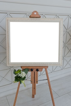 Blank white photo frame on easel