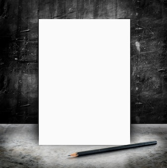 Blank White poster and pencil in a glossy concrete floor and black grunge cement wall