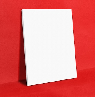 Blank white poster canvas frame leaning at red concrete