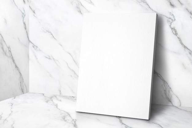 Blank white poster canvas in white glossy marble floor leaning at wall