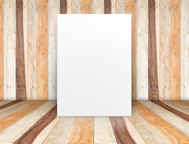 Blank white poster leaning at wooden wall on plank floor