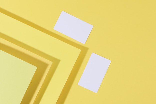 Blank white rectangular business card on creative yellow background from sheets of paper with shadow, top view
