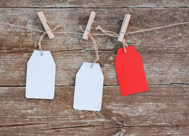 Blank white and red paper tags attached with wooden clothespins to rope