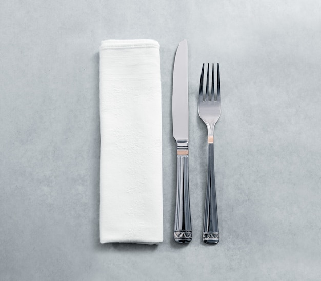 Blank white restaurant napkin mockup with knife and fork, isolated