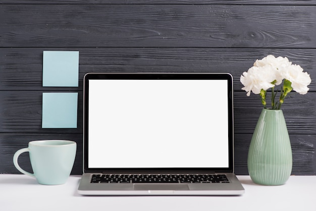 Blank white screen laptop; flower vase; cup on white desk against wooden black wall