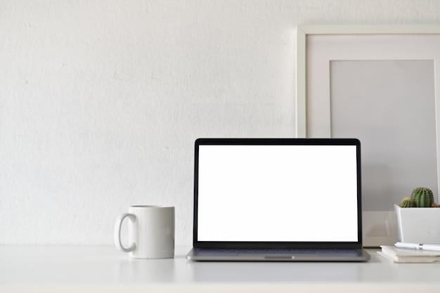白い机のワークスペースに事務用品と空白の白い画面ノートパソコン。