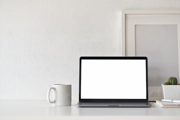 Blank white screen laptop with office supplies on white desk workspace.