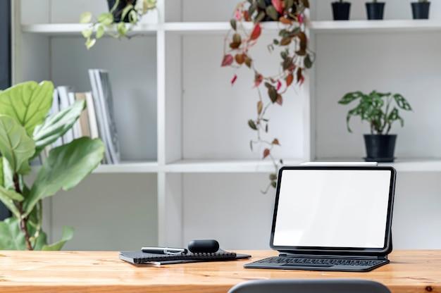 거실에 매직 키보드, 가제트, 하우스온 나무 테이블이 있는 빈 흰색 화면 태블릿.