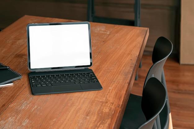 Пустая белая таблетка экрана с волшебной клавиатурой на деревянном столе в гостиной с винтажным стилем.