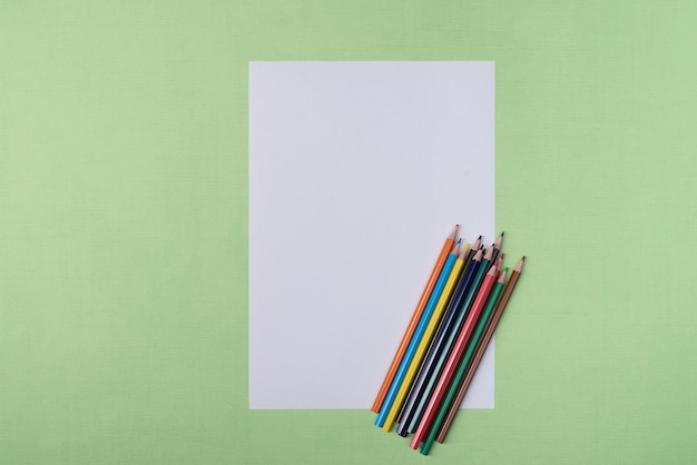 A blank white sheet and colored pencils for drawing on a plain textured background with space
