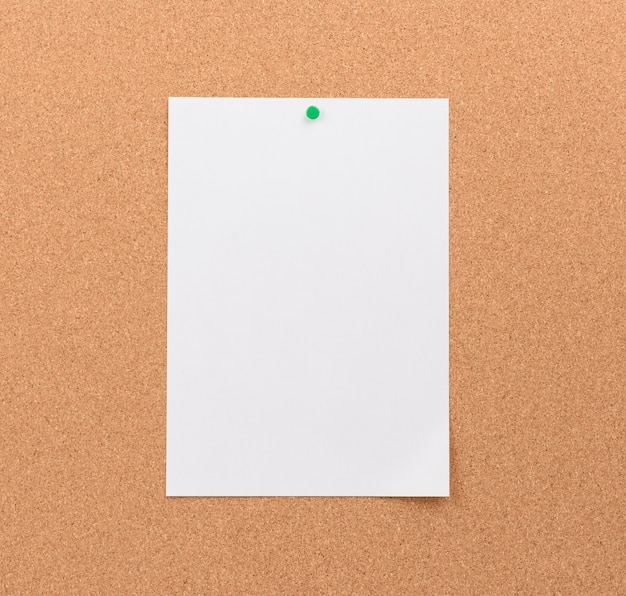 Чистый белый лист бумаги с зеленой кнопкой на коричневом фоне, копией пространства