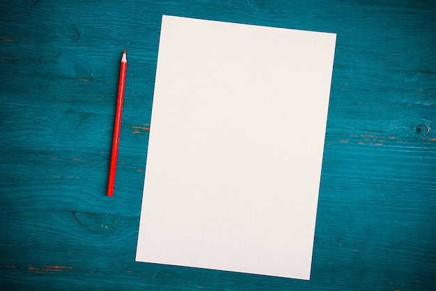 A blank white sheet and pencil for drawing on a wooden background