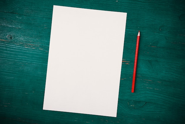 A blank white sheet and a pencil on green wooden background top view