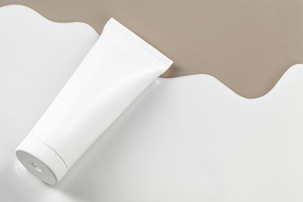 베이지 색 배경에 빈 흰색 스킨 케어 제품 튜브