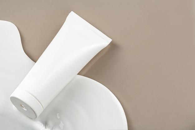 ベージュの空白の白いスキンケア製品チューブ