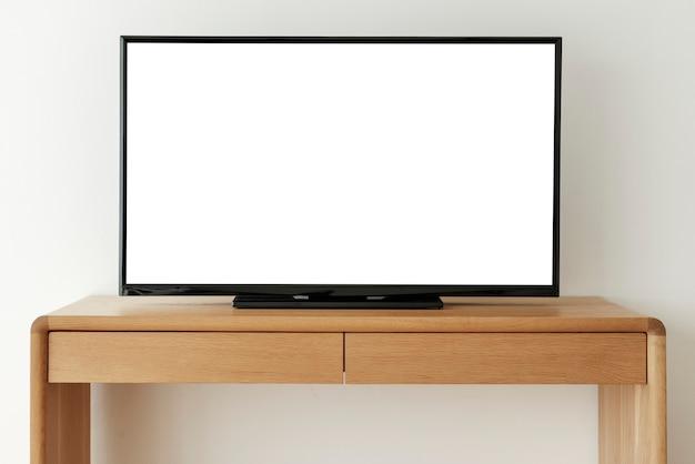 Schermo televisivo bianco vuoto su un tavolo di legno