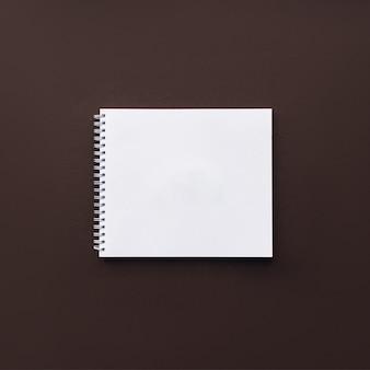 Пустая белая спиральная тетрадь на коричневой поверхности. макет., канцелярские принадлежности на доске.