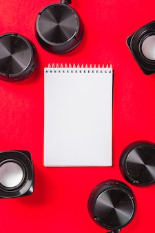 Blank white spiral notepad with headphone and speaker on red background