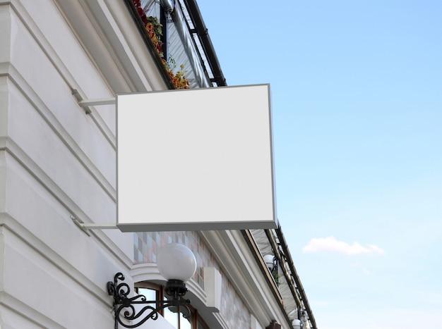 Пустой белый квадратный знак на стене, небо