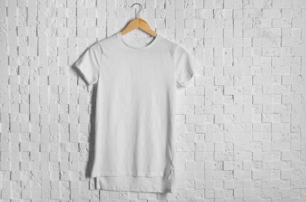 가벼운 질감 벽에 빈 흰색 티셔츠
