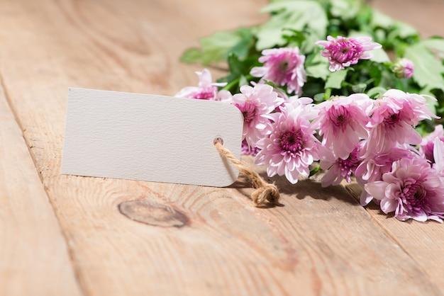 Пустая белая бирка бумаги с цветными цветами на деревянных фоне. вид сверху. макет
