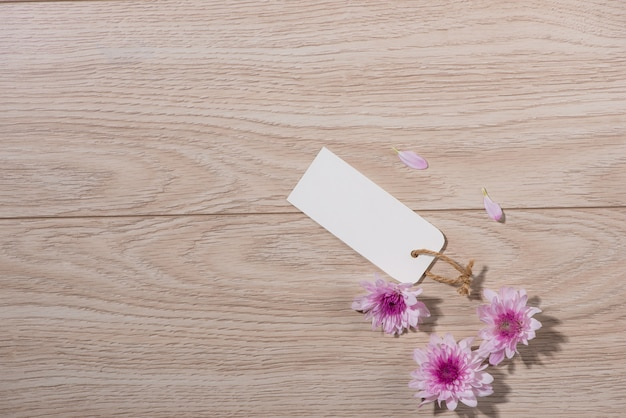 Blank white tag paper with color flowers on wooden background. top view. mock up