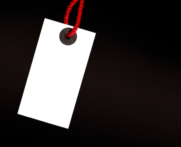 Blank white tag on red thread on black background