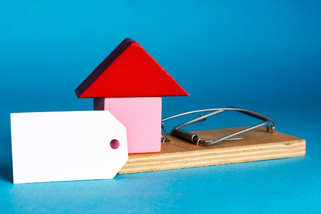 Blank white tag and a small house in a mousetrap. real estate insurance. investment in real estate. residential and commercial real estate fraud. place for your text. high quality photo