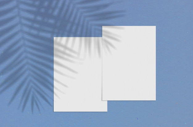 Blank white vertical paper sheet 5x7 inches with palm shadow overlay. modern and stylish greeting card or wedding invitation mock up. color of the year 2020 classic blue