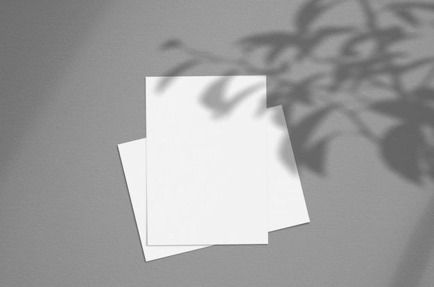 Пустой белый вертикальный лист бумаги 5x7 дюймов с наложением тени дерева.