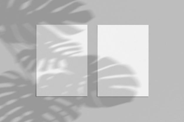 影付きの灰色の背景に空白の白い縦用紙5x7。モダンでスタイリッシュなグリーティングカードや結婚式の招待状のモックアップ