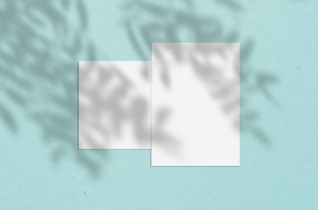 Чистый белый вертикальный бумажный лист с наложением тени дерева.