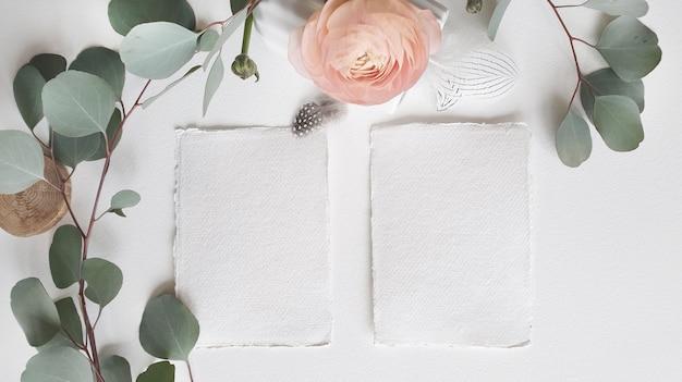 空白の白いウェディンググリーティング招待状カードシルバーユーカリの葉の枝、織り目加工のペーパーテーブルの背景に赤面ピンクのキンポウゲラナンキュラスの花。エレガントでモダンなテンプレートフラット横たわっていたトップビュー