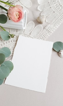Blank white wedding greeting invitation card  silver eucalyptus leaves branch, blush pink buttercup ranunculus flower on textured paper table backgound. elegant modern template flat lay top view