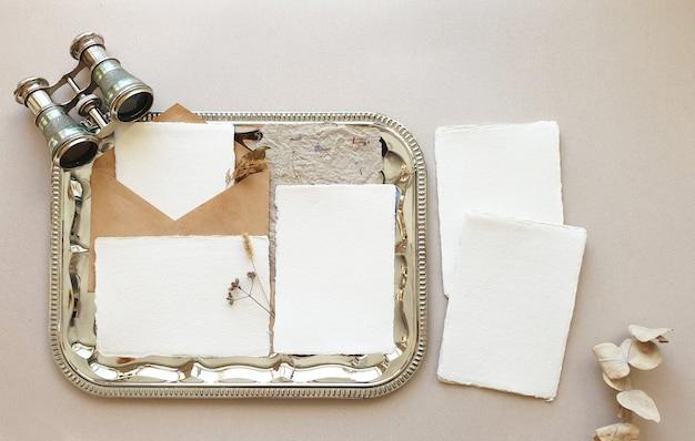 空白の白い結婚式挨拶招待状クラフトエンベロープとモックアップ、ユーカリの葉をテクスチャテーブル背景に残します。ブランドアイデンティティのエレガントでモダンなテンプレート。フラット横たわっていた、トップビュー
