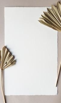 織り目加工のテーブル背景に乾燥したヤシの葉で空白の白い結婚式招待状のモックアップ。ブランドアイデンティティのエレガントでモダンなテンプレート。トロピカルなデザイン。フラット横たわっていた、トップビュー