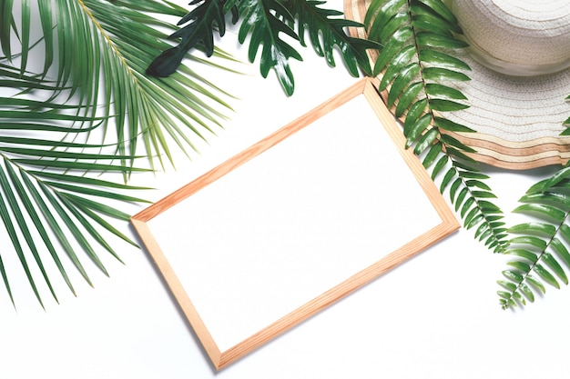 Blank white wood frame with tropical leaf and big hat isolated