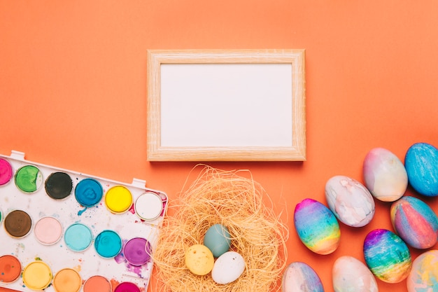 Blank white wooden frame with watercolor paint box and easter eggs on an orange background
