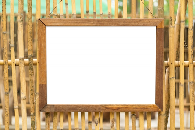 Blank white wooden photo frame on bamboo wall