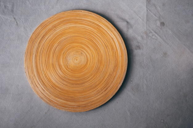 Blank wood cutting board on table with gray tablecloth with stain background.