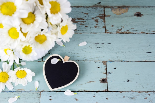 Blank wood heart and daisy flowers on old wood