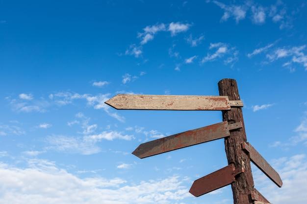 Blank wooden arrow shape signs against blue sky,old wooden direction signs against blue sk