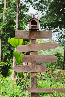 Blank wooden arrows signpost with nest
