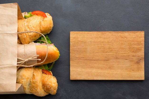 Blank wooden board and sandwiches