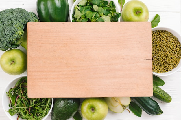 Blank wooden chopping board over the green vegetables and fruits