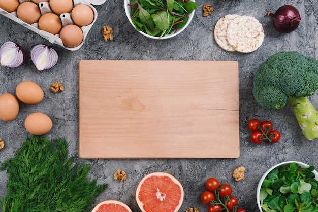 Blank wooden chopping board with raw vegetables and puffed rice cake over concrete backdrop